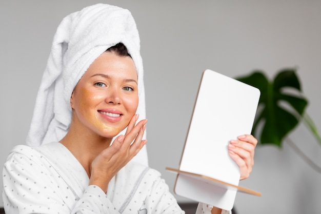 Front view of woman in bathrobe applying skincare with towel on head
