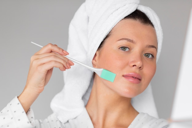 Front view of woman in bathrobe applying skincare