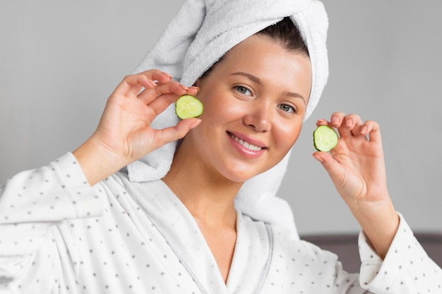 Front view of woman in bathrobe holding cucumber slices