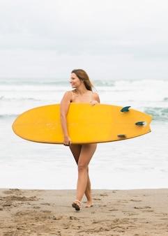 Vista frontale della donna in spiaggia tenendo la tavola da surf per coprire il suo corpo