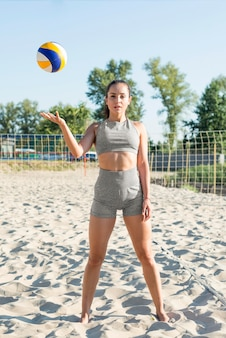 Front view of woman on the beach posing with volleyball