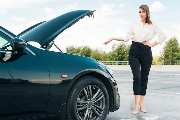 Front view of woman and black car