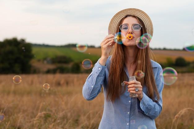 Vista frontale della donna che soffia bolle all'aperto nella natura