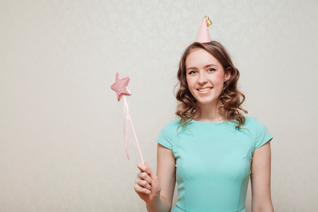 Front view woman in blue dress wearing a party hat