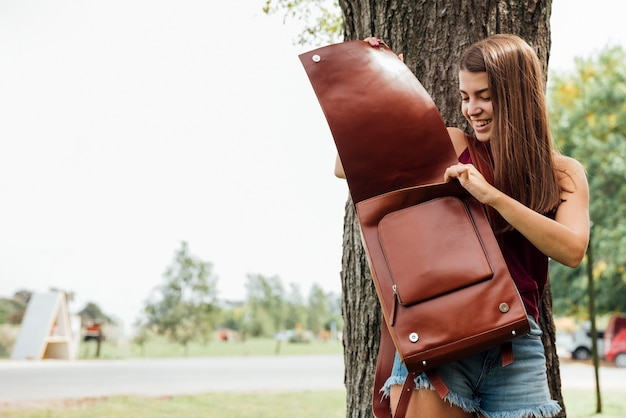 Front view of woman checking her backpack