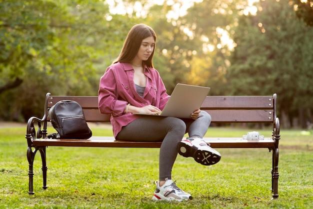 Donna di vista frontale che controlla il suo laptop mentre era seduto sulla panchina