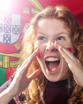 Front view of woman cheering with the portugal flag on her face