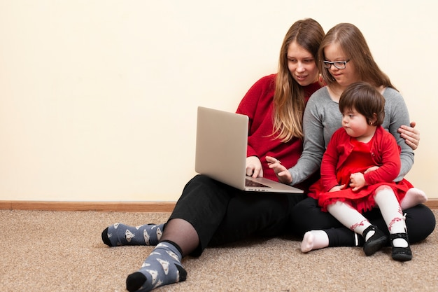 Front view of woman and children with down syndrome looking at laptop