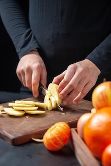 Vista frontale della donna che taglia a pezzi la frutta fresca della mela in vassoio di legno sul tavolo da cucina