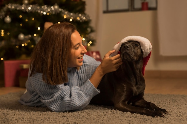 Front view of woman on christmas with her dog wearing santa hat