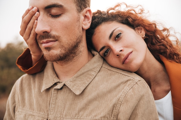 Front view woman covering man eye
