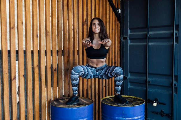 Front view of woman crouching on barrels