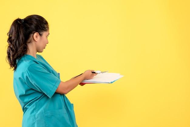 Vista frontale della donna medico in uniforme dando documenti in piedi sulla parete gialla