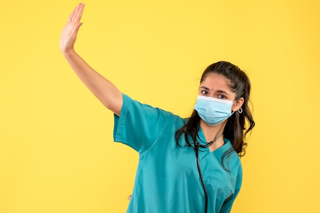 Front view of woman doctor in uniform hailing someone standing on yellow wall