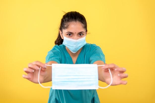 Vista frontale della donna medico in uniforme che tiene la maschera nelle sue mani sulla parete gialla
