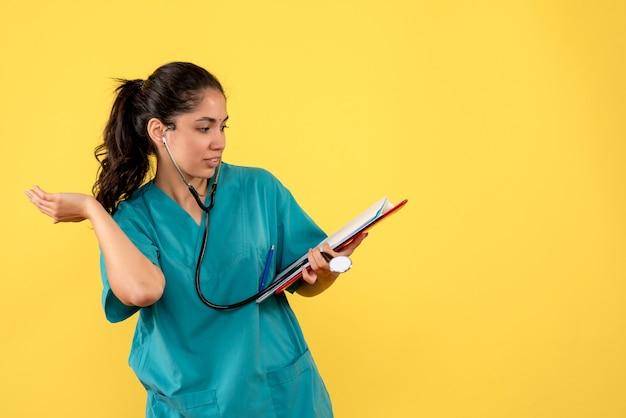 Vista frontale della donna medico in uniforme che tiene i documenti in piedi sulla parete gialla