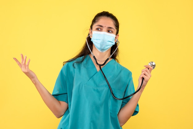 Vista frontale del medico della donna in uniforme che tiene lo stetoscopio in piedi sulla parete gialla