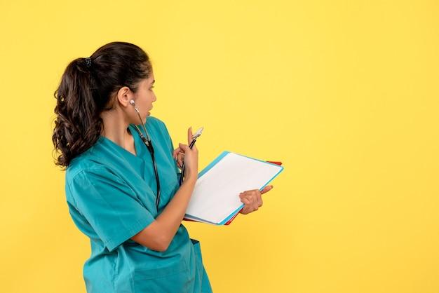 Vista frontale della donna medico in uniforme guardando dietro con documenti sulla parete gialla