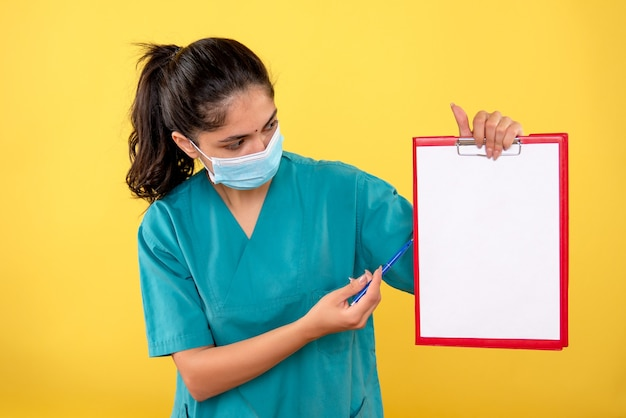 Vista frontale della donna medico in uniforme che mostra qualcosa su carta sulla parete gialla