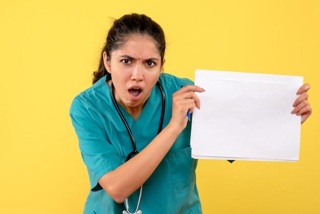Vista frontale del medico della donna con la bocca aperta che mostra i documenti sulla parete gialla