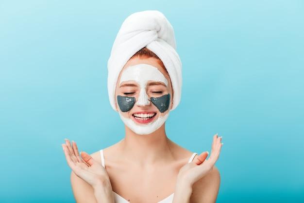 Vista frontale della donna che fa il trattamento termale con gli occhi chiusi. studio shot di affascinante ragazza con la maschera per il viso in piedi su sfondo blu.