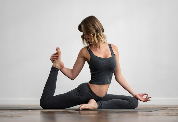 Front view of woman doing yoga at home on mat