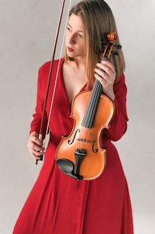 Front view of woman in dress holding violin