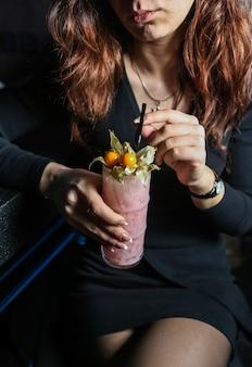 Вид спереди женщина пьет молочный коктейль с физалисом и соломой