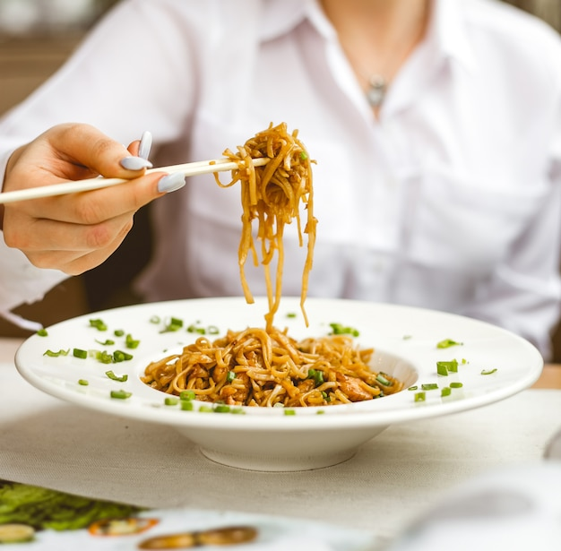 Front view woman eats chinese noodles in sauce with green onions