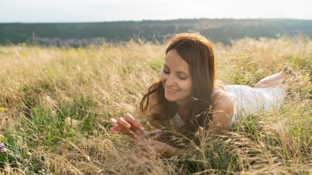 Front view of woman enjoying the grass in nature