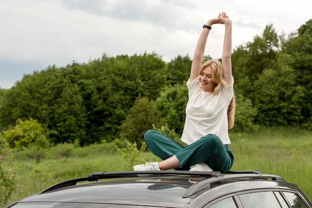 車の上にポーズをしながら自然を楽しむ正面女性