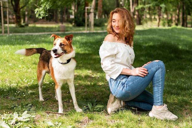 Женщина вид спереди, наслаждаясь прогулкой в парке с собакой