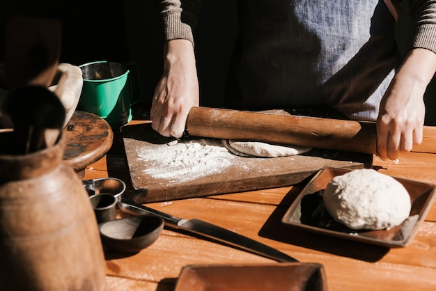 Front view of woman flattening dough