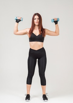 Front view of woman in gym attire exercising with weights