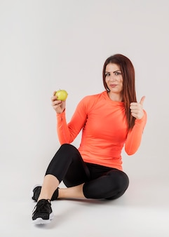 Front view of woman in gym attire giving thumbs up while holding apple
