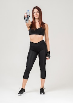 Front view of woman in gym attire posing while holding up a bottle of water