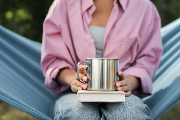 Vista frontale della donna in amaca con libro e tazza