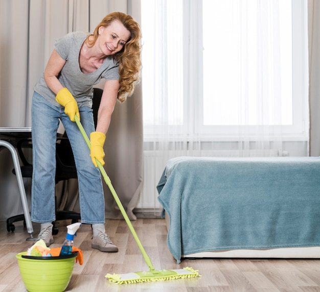 Front view of woman happily mopping the floor