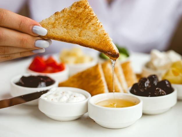 Vista frontale una donna fa colazione toast fritto con marmellata di panna acida al burro miele e olive su un piatto