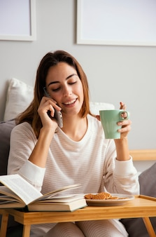Front view of woman having coffee at home and talking on the phone at home