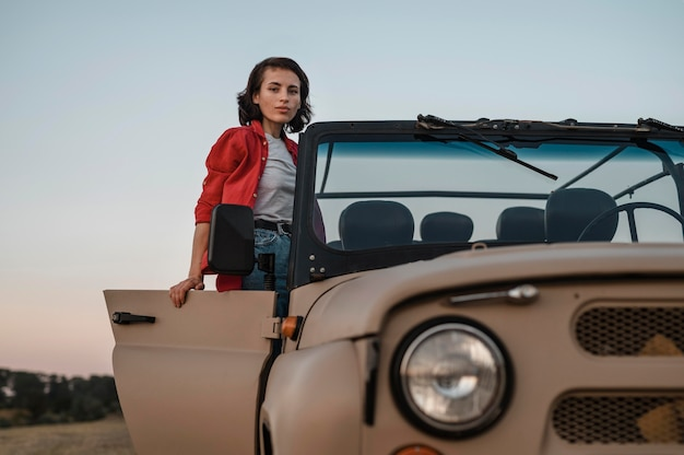 Front view of woman having fun traveling alone by car