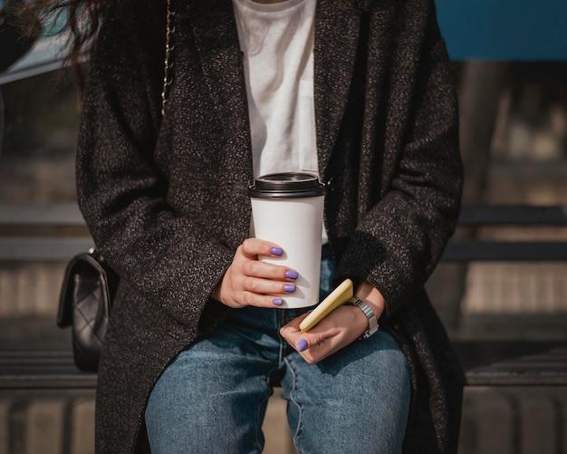 コーヒーを持ってバスを待っている正面図の女性