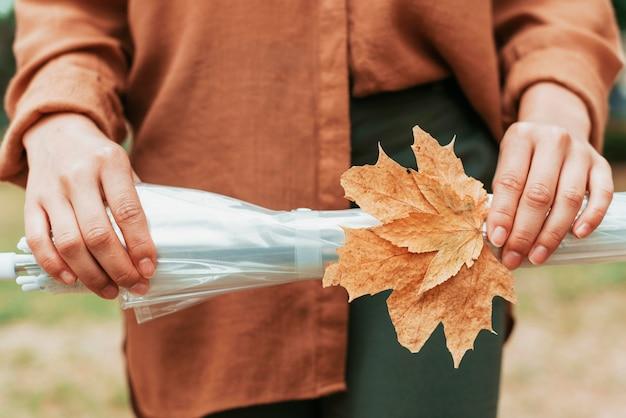 Вид спереди женщина, держащая лист и зонтик