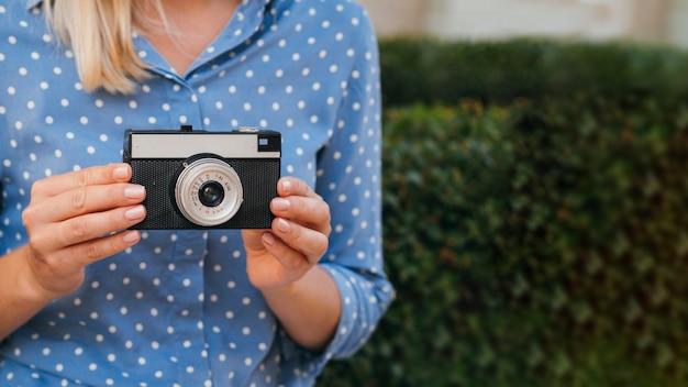 レトロな写真カメラを保持している正面の女性