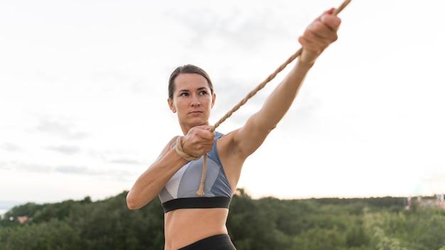 Вид спереди женщина, плотно держащая веревку