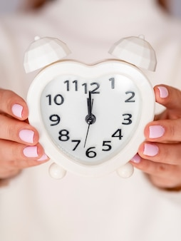 Front view woman holding alarm clock