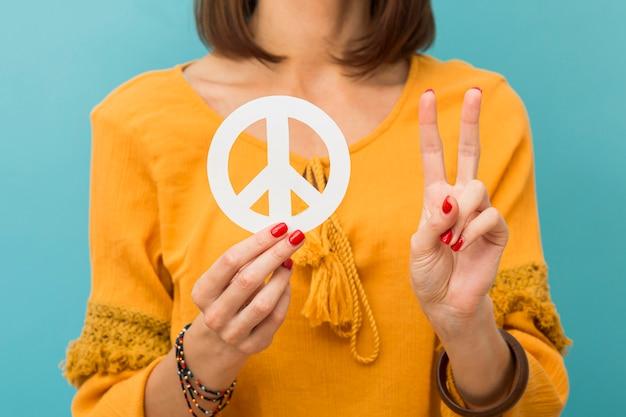 Женщина вид спереди держа и делая знак мира