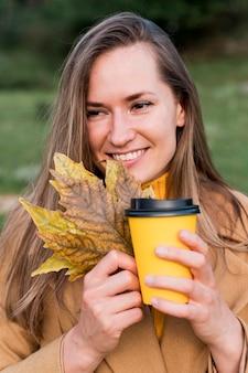 Вид спереди женщина, держащая осенние листья и чашку кофе