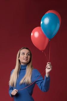 Женщина вид спереди держит воздушные шары