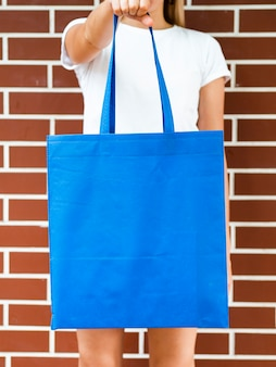 Front view woman holding a blue bag
